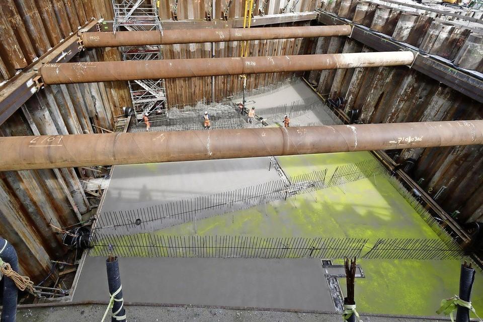 De enorme bouwkuip met betonvloer en gele substantie.