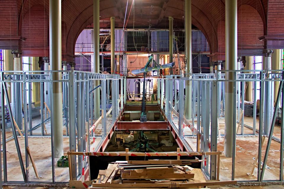 Vanaf de begane grond wordt met een kraan een nieuwe lading hotelkameronderdelen naar de eerste verdieping gehesen.
