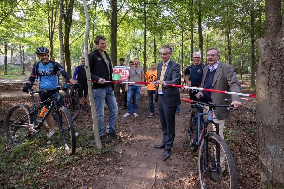 Wethouder Erwin Jansma opent het verbindingsstuk tussen de mtb-routes van Hooge en Lage Vuursche. Frank Baudet (links) van MTB Utrechtse Heuvelrug en Per Insinger van landgoed Pijnenburg kijken toe.
