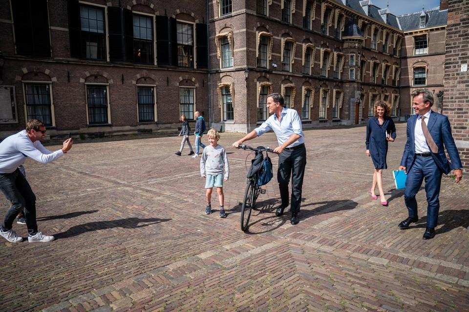 Heel Hollands en heel erg Mark Rutte: met de fiets aan de hand even poseren voor een 'fan' op het Binnenhof.