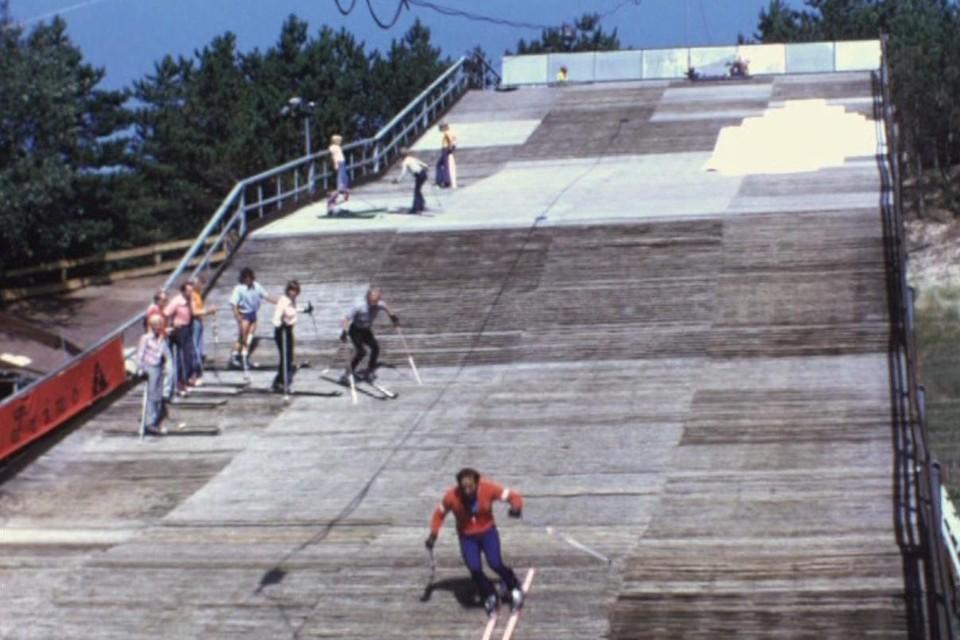 De instructeur doet voor hoe het moet op de borstelbaan van Il Primo in Bergen. Zijn skiklasje staat links op de baan opgesteld.