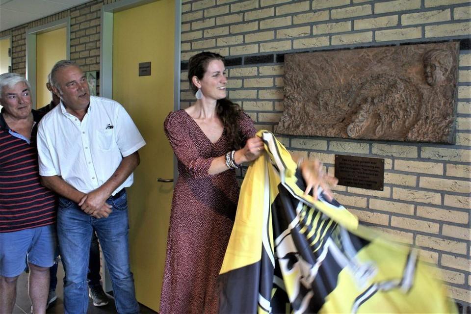 Bram Visser en Gidus van Swaluw kijken toe hoe Vera Koedooder de plaquette van Theo Koomen in de VVW kantine onthuld.