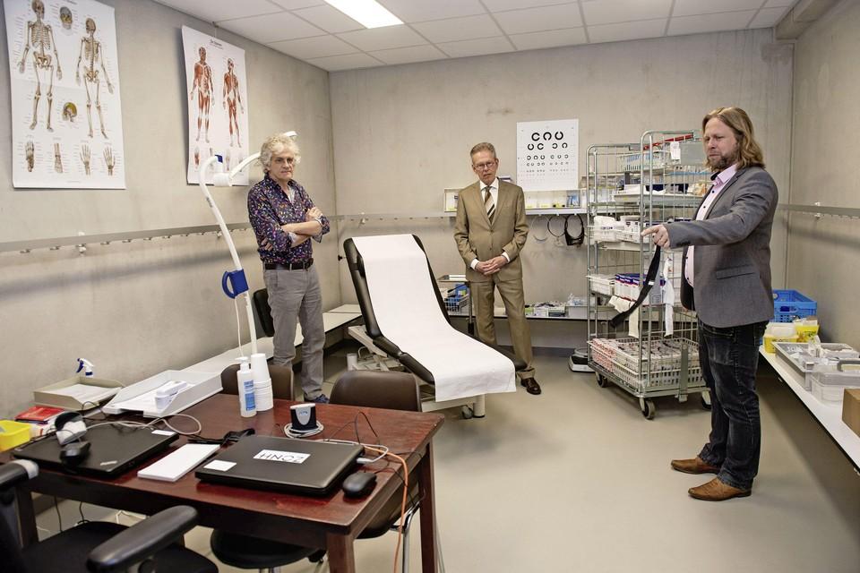 Erik Schoofs (r) van Huisartsenzorg Zaanstreek-Waterland leidt burgemeester Don Bijl van Purmerend rond in sporthal De Beuk. Links arts Joost Zaat.