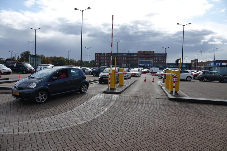 Auto tegen muurtje zorgt voor file op parkeerterrein bij winkelcentrum Heerhugowaard
