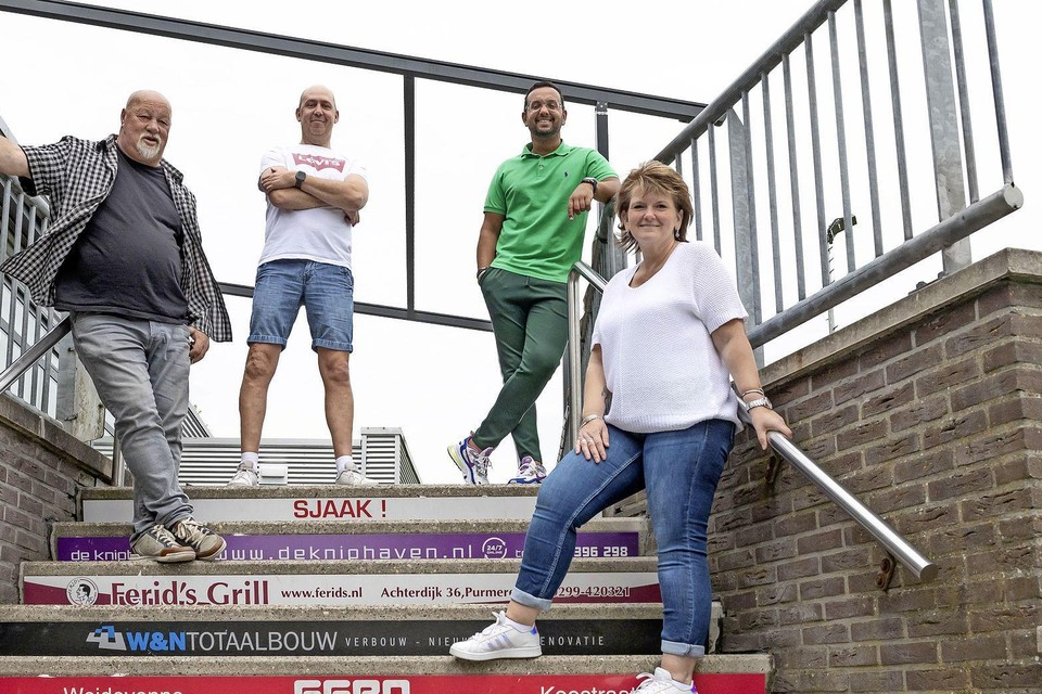 Met op de achtergrond het geraamte van de overkapping poseren (vanaf links) John Bakx, Andre Persenaire, Brian van Gils en Nel Persenaire op de gesponsorde trap.