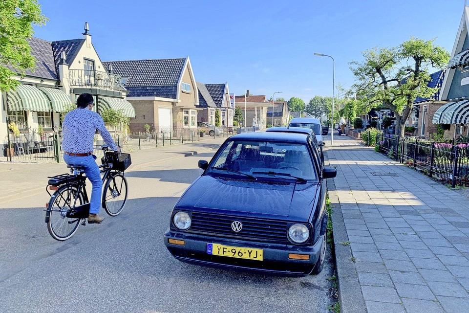 Een fietser passeert geparkeerde auto's op het Twijver in Venhuizen.