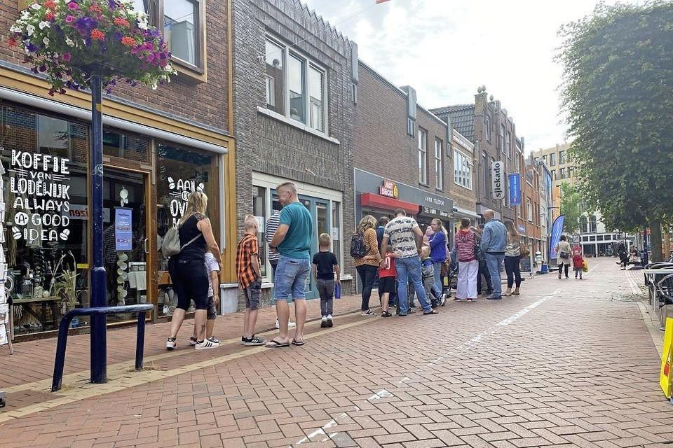 Het gezin De Vries sluit aan achter in de rij voor de nieuwe winkel Just Bricks