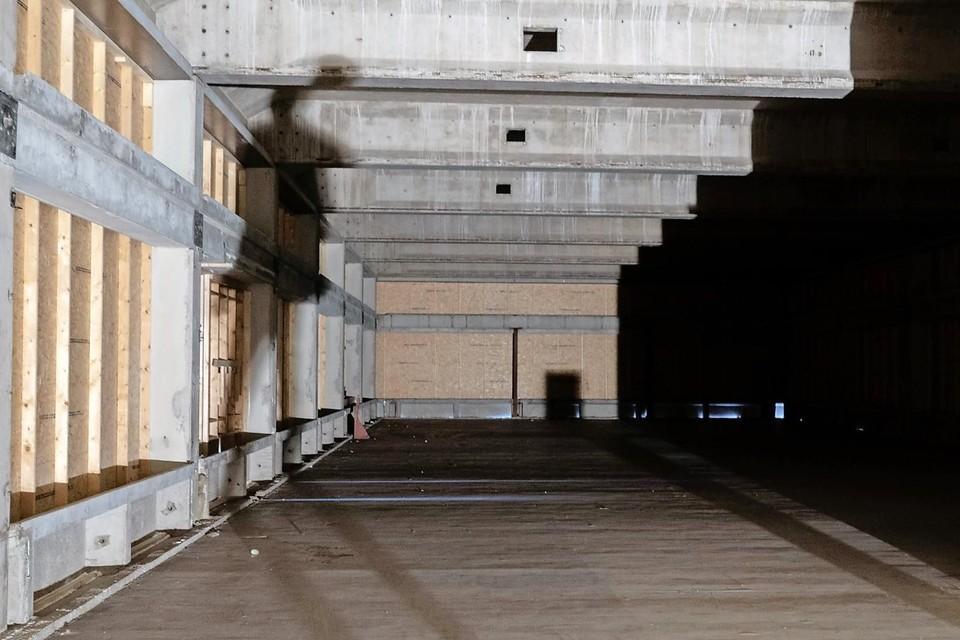 Donker, OSB-platen, veel beton en silhouetten in het'grote niets' van het oude postkantoor.