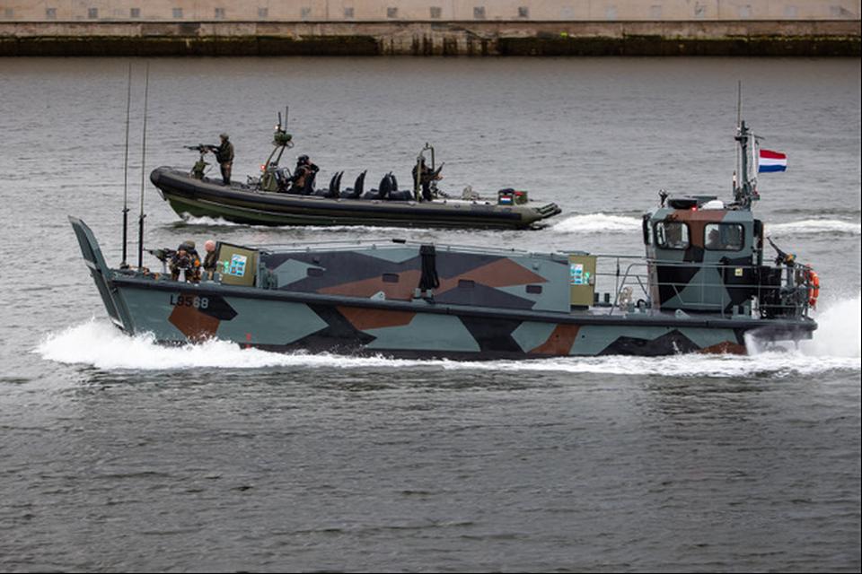 Mariniers snellen over het water op een Landing Craft Vehicle & Personnel-vaartuig en een Fast Raiding Interception Special Forces Craft-vaartuig.