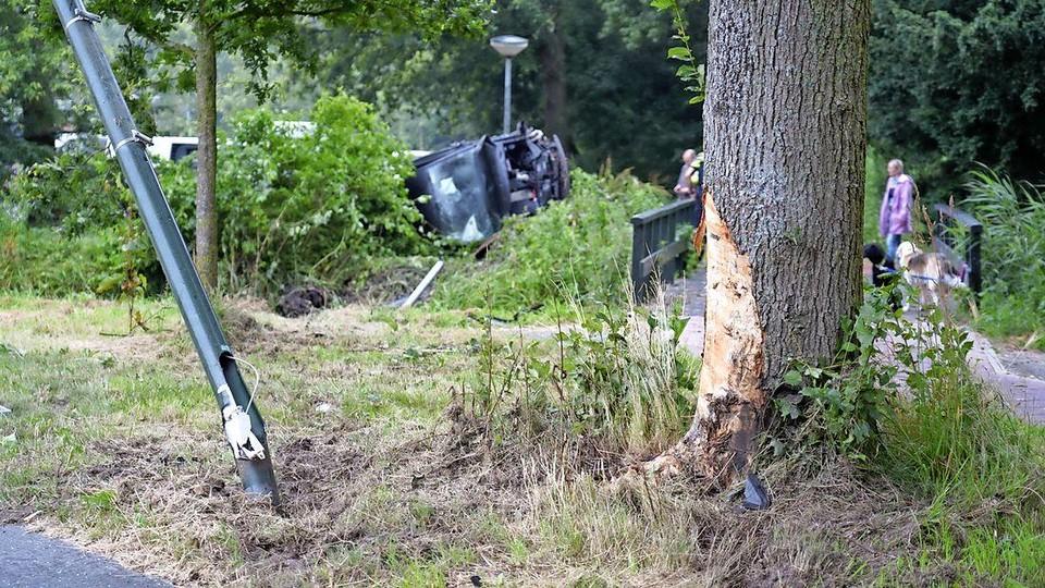 De auto, op de achtergrond op z'n kant, raakte eerst een lantaarnpaal en een boom.