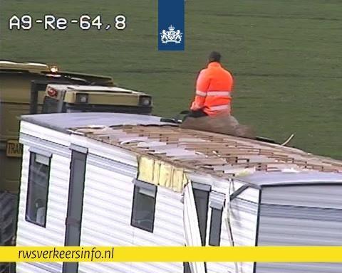 De eigenaar van de stacaravan op het stukje dak dat nog over is.