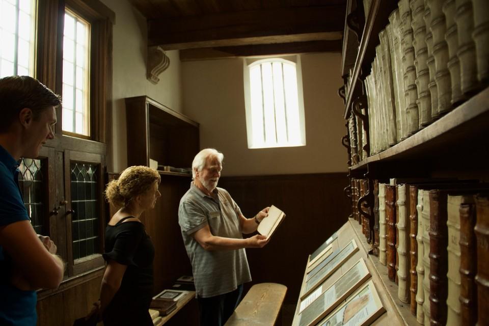 Dennis Heijnen en Inge van Dijk bekijken met Jaap Hoekstra de boeken in de Librije.