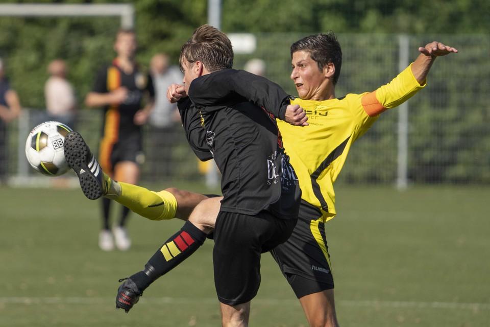 Ron Baltus (rechts), aanvoerder van Geel Zwart, tikt de bal net weg voordat doelpuntenmaker Mark de Vries hetzelfde kan doen.