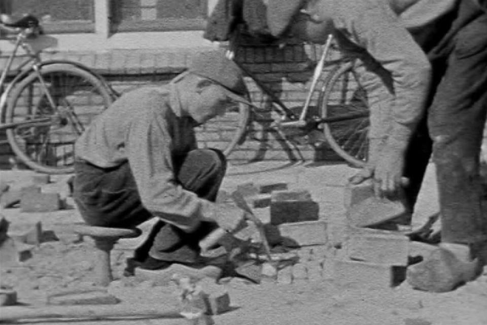 Zittend op een speciaal stratenmakerskrukje, met onderaan een bol pootje, leggen de heren gestaag kilometers klinkers. Tegen de muur staan hun fietsen met daaroverheen hun jasjes.