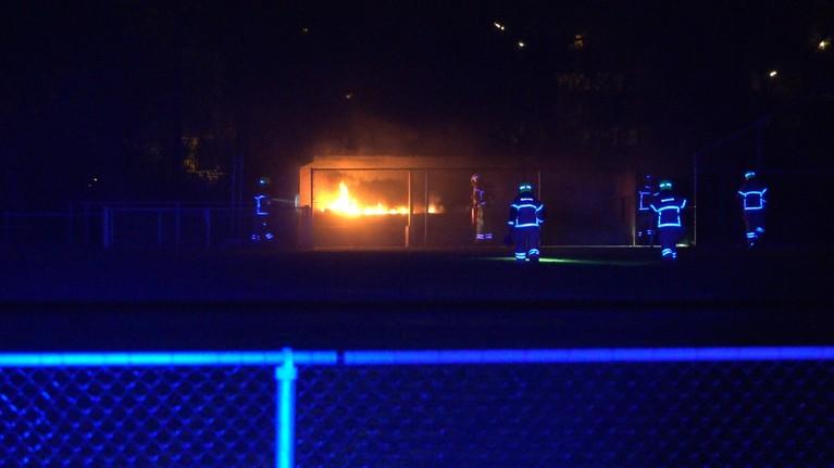 Brandweerlieden klimmen over hek om brand te blussen in dug-out op Sportpark De Vork in Heerhugowaard