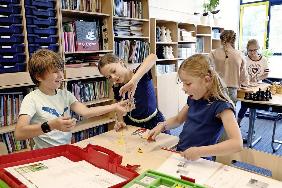 Een groepje leerlingen mag zelf aan de slag met de techniekkoffer over magnetisme.