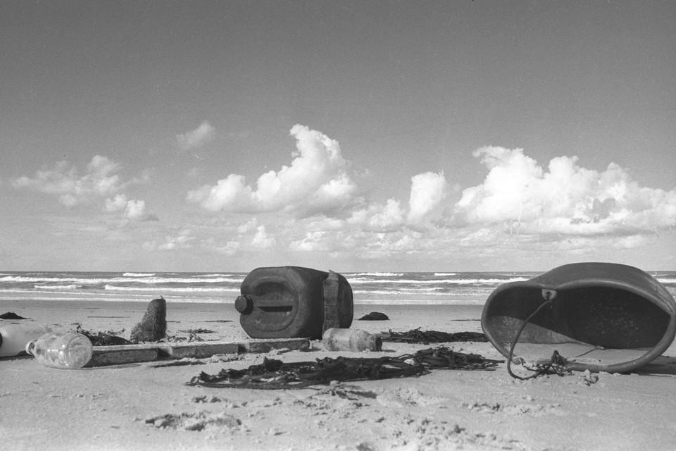 Plastic flessen , jerrycans en emmers aangespoeld op het strand.