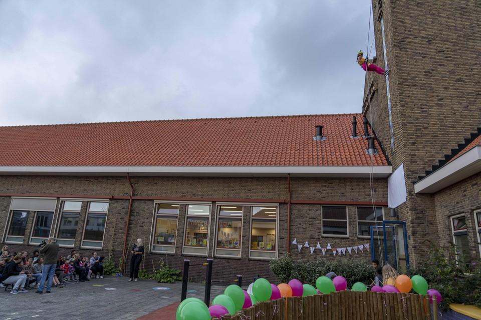 Juf Angèlle Selhorst daalt de toren van de (voormalige) Tuindorpschool af, op weg naar het doek dat de nieuwe naam bedekt.