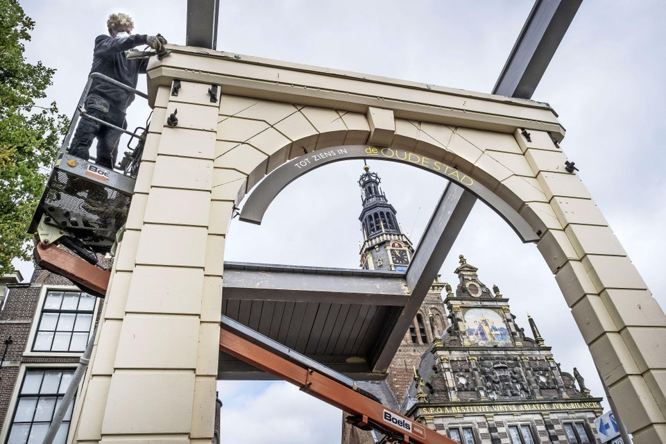 Paul van der Meij is met een hoogwerkertje bezig met de schuurklus op hoogte van de Bathbrug.