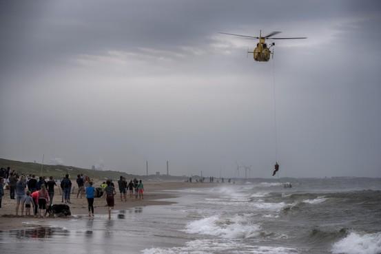 Reddingsbrigades oefenen bij Castricum, Kustwachtheli vist drenkelingen uit zee