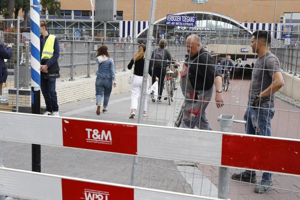 Terwijl de hekken op het fietspad worden geplaatst, glippen er nog net wat mensen doorheen.